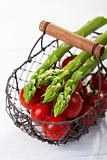 wire basket with tomatoes and asparagus