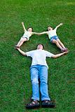 happy asian family lying and playing on the grass