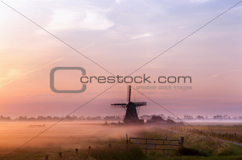 Dutch windmill in fog in the early morning