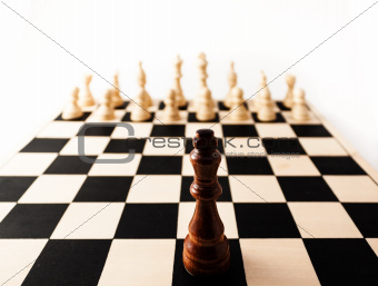 Single chess piece the King standing up against many of his enemies.