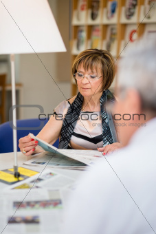 Old woman reading newspaper with husband in library