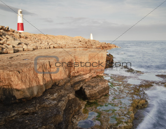 Victorian lighthouse on promontory of rocky cliffs during stunni