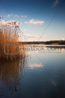 Lovely landscape image looking across calm lake with sky reflect