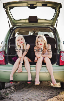 Two beautiful blonde girls sitting in trunk of broken car