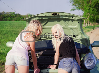 Two sexy blonde girls stand by the broken car. Rear view