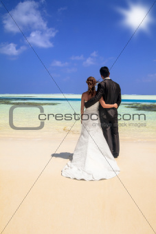 Bride and groom on idyllic tropical beach