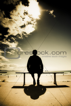 Young Man In Silhouette Sitting In The Sun