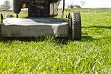 Push mower stopped in front of a small patch of grass on a finished lawn