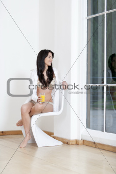 Young woman sat on chair in underwear