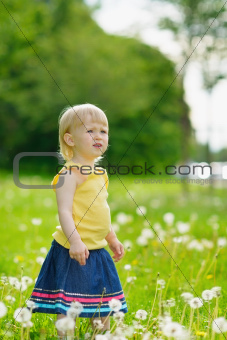 Baby girl on dandelions field looking on copy space