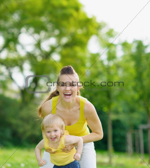 Portrait of happy mother and baby girl in park