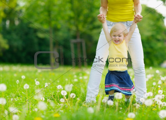 Mother playing with baby girl on dandelions field