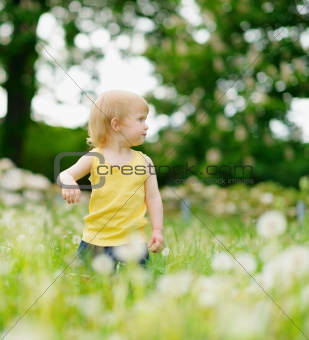 Baby girl on dandelions field looking back