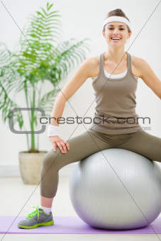 Fitness woman sitting on fitness ball