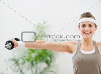Smiling athletic woman making exercise with dumbbells