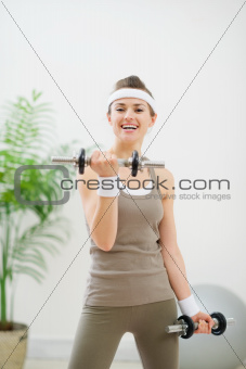 Healthy athletic woman making exercise with dumbbells
