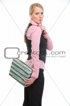 Woman holding present box behind back and showing shh gesture