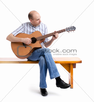 Handsome young man playing guitar, sitting on a bench