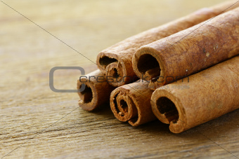 Cinnamon sticks on wooden background