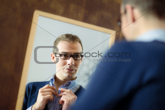 Young man dressing up and looking at mirror