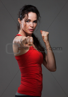 Attractive woman throwing a pucnh