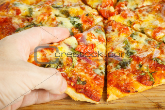 Hand grabbing slize of pizza