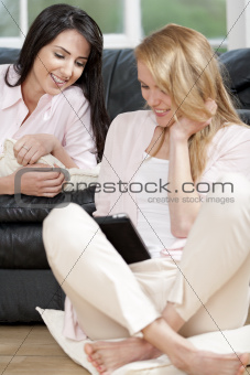 Two friends sharing a computer tablet and chatting