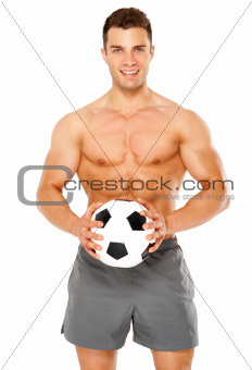 Fit muscular man with soccer ball on white