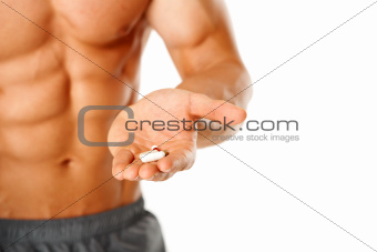 Close up of muscular man torso with hand full of pills