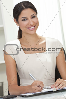 Hispanic Latina Woman or Businesswoman in Office Writing