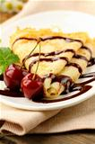 Sweet pancake with chocolate sauce and cherries