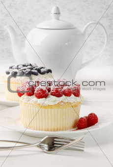 Cupcakes with raspberries and cream on table