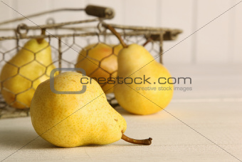 Fresh ripe pears in basket on table