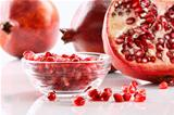 Ripe pomegranates and glass bowl of seeds on white