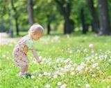 Baby gathering dandelions in park