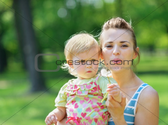 Young mother and baby blowing away dandelion