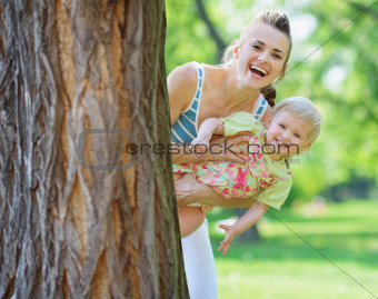 Smiling mother and baby looking out from tree