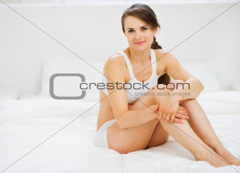 Portrait of healthy woman sitting on bed