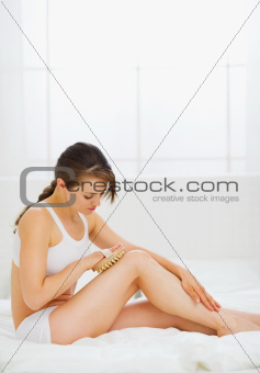 Slim woman sitting on bed and making legs massage
