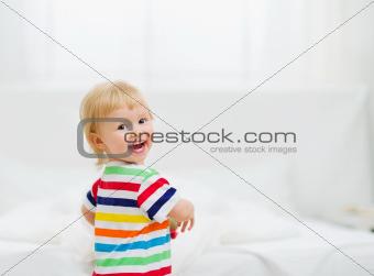 Portrait of smiling baby in bedroom