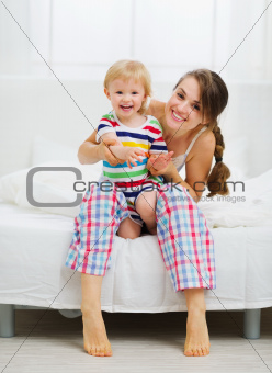 Portrait of smiling mother and baby in bedroom