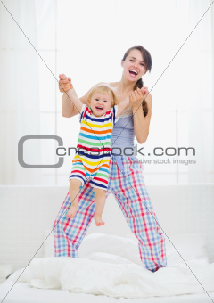 Mom playing with baby in bedroom