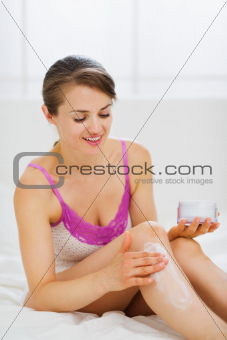 Self caring woman applying creme on leg