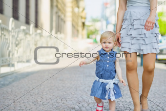 Baby with mother walking in city
