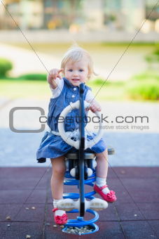 Baby swing on horse on playground and pointing in camera