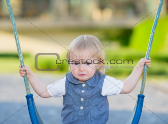 Portrait of unhappy baby sitting on swing