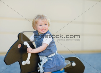 Baby swing on horse on playground and looking on copy space