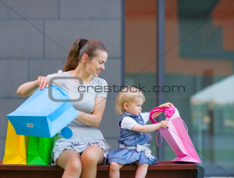 Mother and baby looking into shopping bag