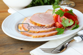 Baked ham served with salad and herbs