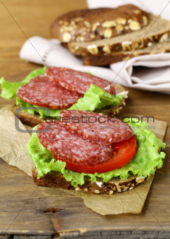 sandwich with sausage salami, lettuce and tomato